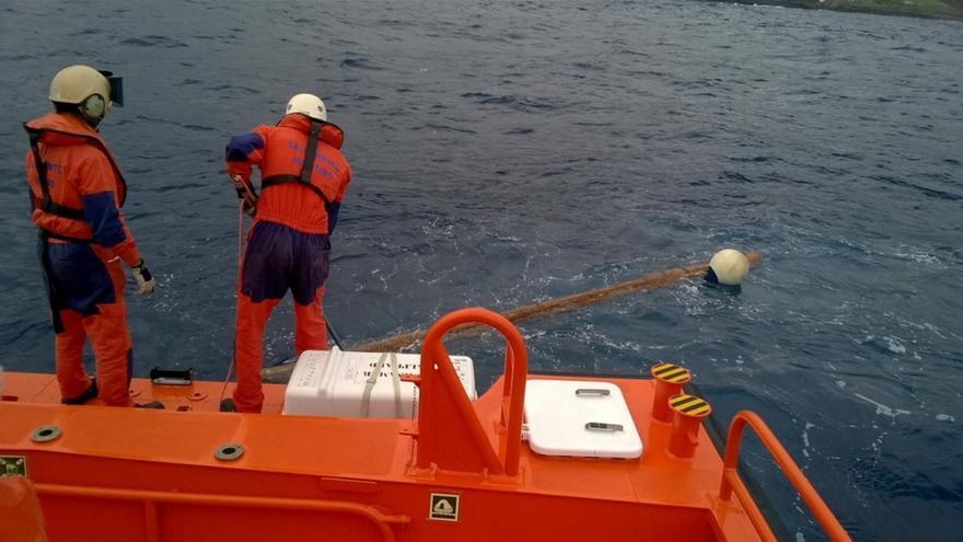 Momento en el que dos miembros de la tripulacion de la embarcación Alphard retiran el tronco. Foto: Salvamento Marítimo.
