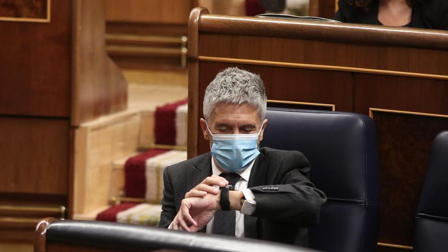 El ministro de Interior, Fernando Grande-Marlaska, consulta la hora durante una nueva sesión de control al gobierno en el Congreso