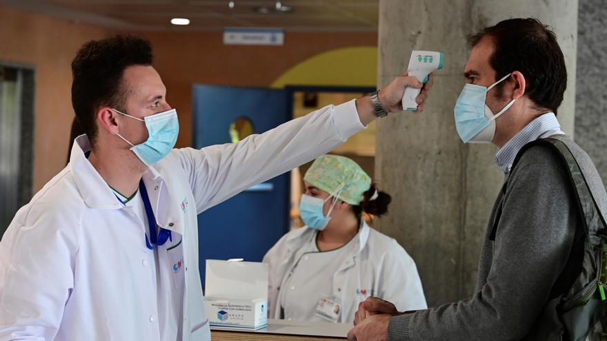 Un sanitario toma la temperatura a un hombre que accede a un recinto hospitalario