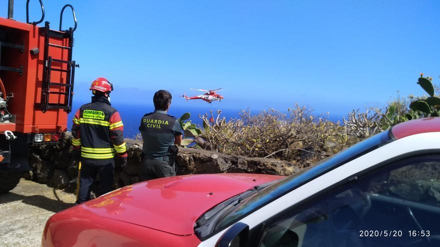 Un bombero y un guardia civil observan una de las descargas de agua del helicóptero del GES en el fuego registrado  este miércoles en el barrio de Los Callejones de Mazo.
