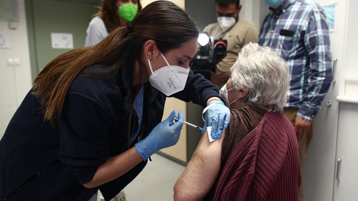 Una sanitaria inyecta la primera dosis de la vacuna de Pfizer contra el coronavirus a una mujer.