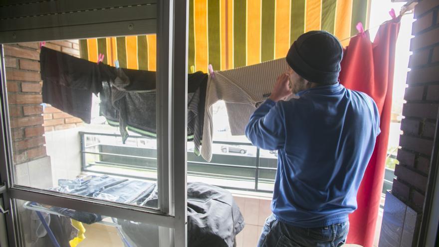 Un beneficiario del programa Hábitat en Córdoba tiende la ropa en su casa.