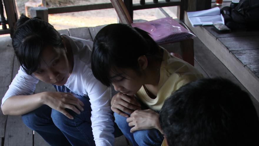 Dos integrantes de una ONG analizan junto a uno de los campesinos expropiados el mapa de las tierras acaparadas./ Alisson da Paz y David Vidad.
