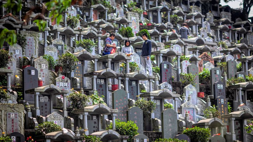 Un grupo de personas visita un cementerio durante la celebración del día de los muertos en China.