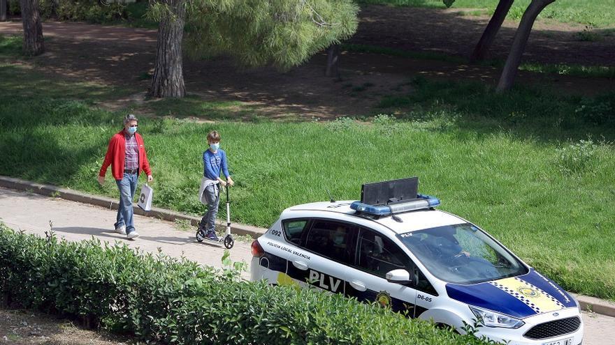Un niño en patinete junto a su padre y un coche de la Policía Local de València en el jardín del Túria.