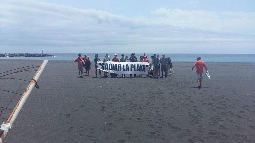 Los ciudadanos ha desplegado una pancarta con el lema 'Salvar la playa. Foto JOSÉ AYUT.