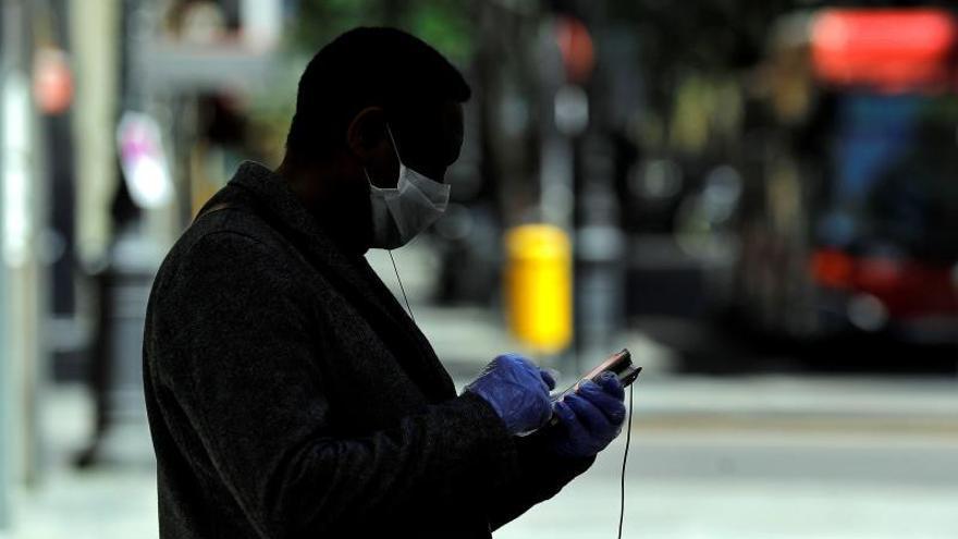 Un hombre su teléfono móvil en una calle de Valencia.