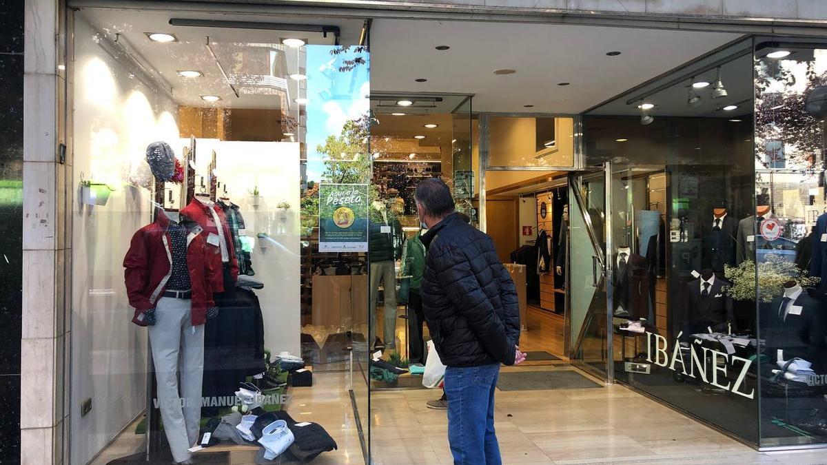 """Un hombre lee el cartel de la campaña """"Agur a la peseta"""" en el escaparate de la tienda Ibáñez."""