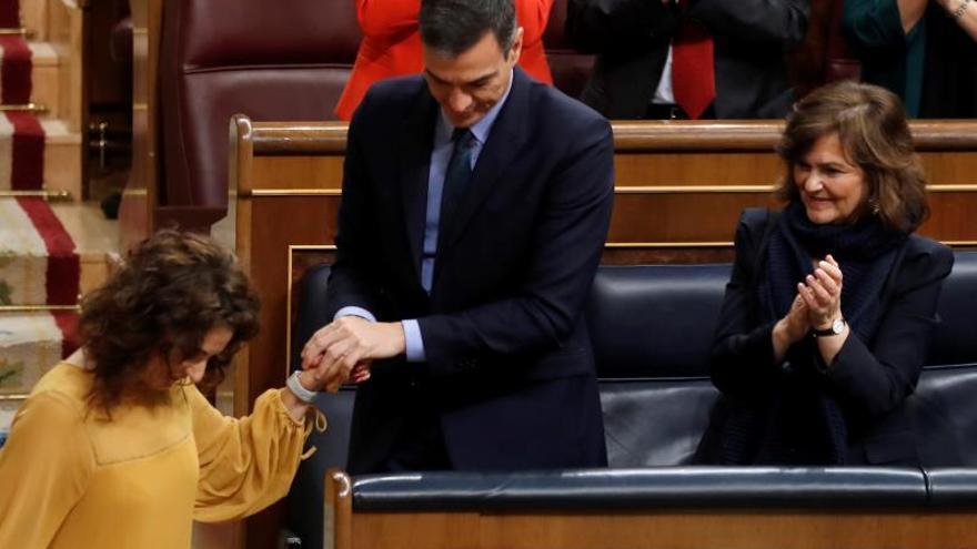 La ministra de Hacienda, María Jesús Montero (i), es felicitada por el presidente del Gobierno, Pedro Sánchez, tras su intervención