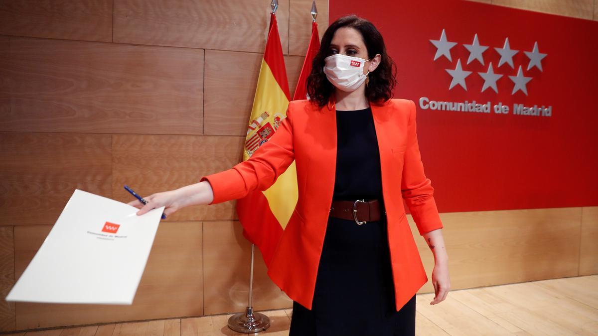 La presidenta de la Comunidad de Madrid, Isabel Díaz Ayuso, entrega unos papeles antes de dar una rueda de prensa. EFE/Emilio Naranjo