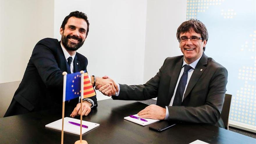 El expresident de la Generalitat Carles Puigdemont estrecha la mano del presidente del Parlament, Roger Torrent, durante su reunión en Bruselas
