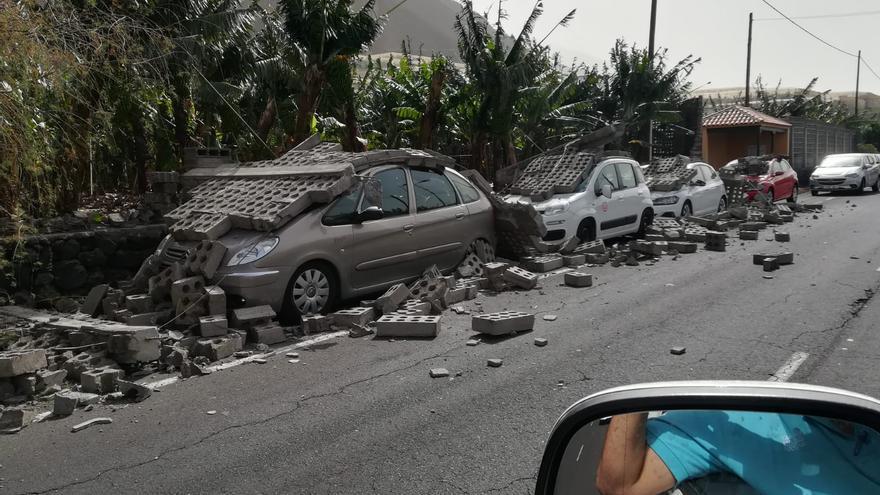 Muro tumbado sobre varios coches en la comarca oeste.