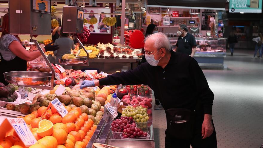 Un cliente señala la pieza de fruta que quiere en una frutería del Mercado Central de Valencia