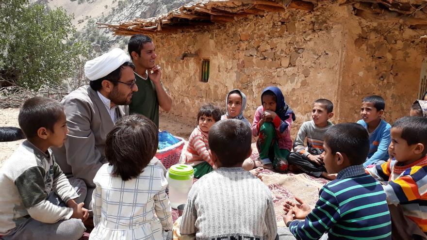 Esmail Azarinejad junto a un grupo de menores en uno de los pueblos de Irán donde lleva a cabo su actividad