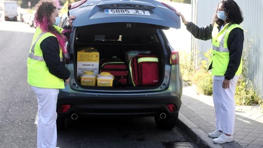 Dos técnicas sanitarias cierran la puerta del vehículo donde tienen el material del Centro de Salud Cerro del Aire en Majadahonda (Madrid) para realizar estudios de seroprevalencia en domicilios