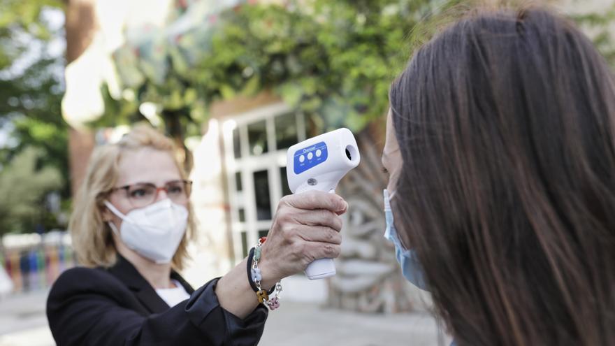 Archivo - Una profesora le toma la temperatura a una alumna, foto de recurso