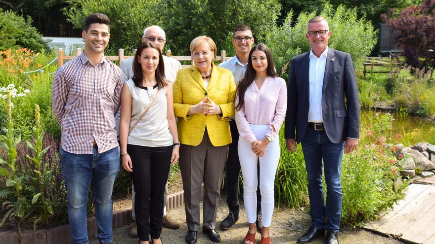 La canciller alemana, Angela Merkel, junto a varios estudiantes que cursan formación en los hoteles de IFA. A la derecha, el Director de IFA Rügen, Thomas Krüger.