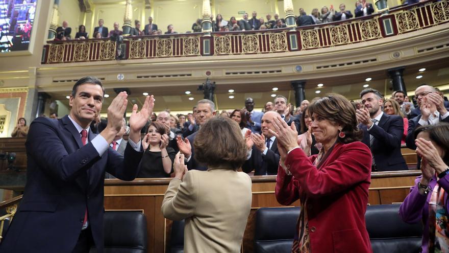 Pedro Sánchez, Carmen Calvo y Dolores Delgado durante la ovación de la bancada socialista tras la investidura.