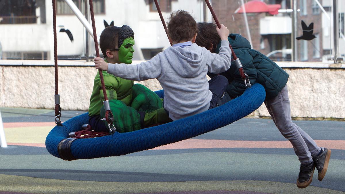 Niños juegan en un parque infantil.
