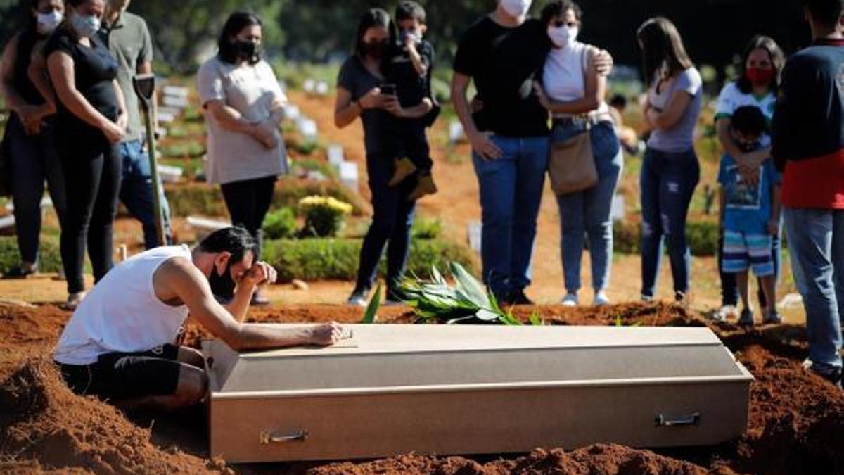 Una familia despide a un familiar durante un entierro 24 de marzo de 2021 en el cementerio Vila Formosa, en Sao Paulo (Brasil).