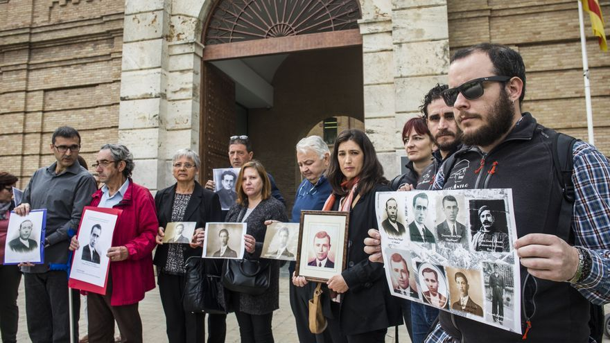 Familiares de fusilados por el franquismo sostienen los rostros de las víctimas frente a la Cárcel Modelo de Valencia