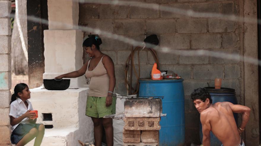 Una familia cocina en uno de los 'Fogones mejorados de adobe'