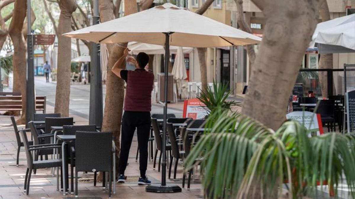 Imagen de archivo de un hostelero, poniendo en marcha una terraza.