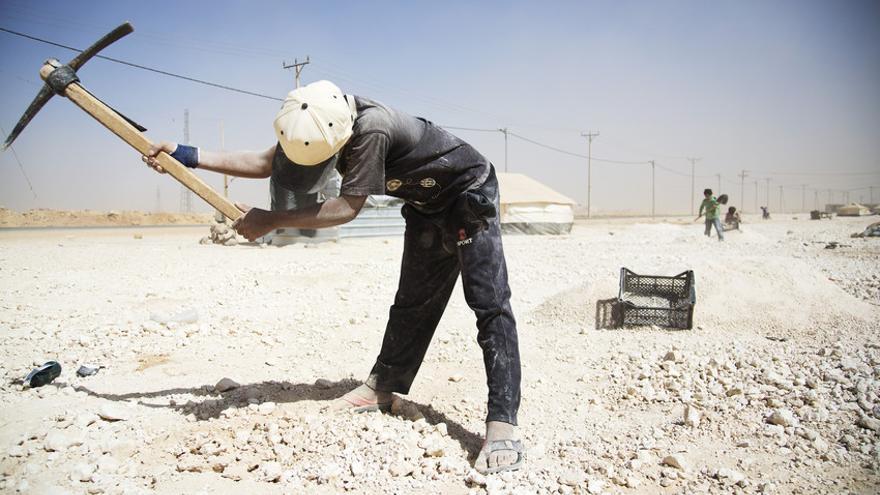 Niño trabajando en el campo de refugiados de Za'atari, Jordania, cavando arena para vende para la construcción. / Rosie Thompson / Save the Children.