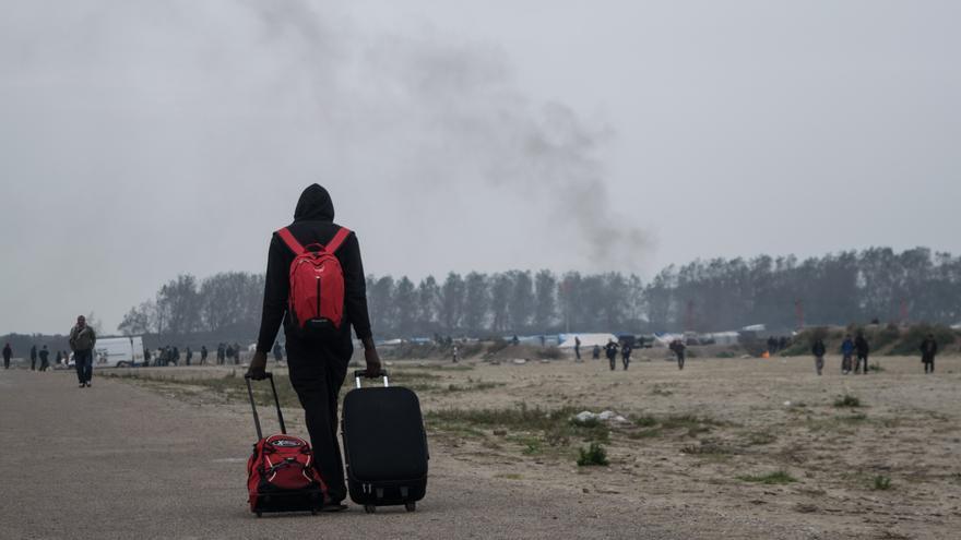 Un hombre con sus maletas se aleja del campamento de refugiados de Calais. | Eduardo Granados