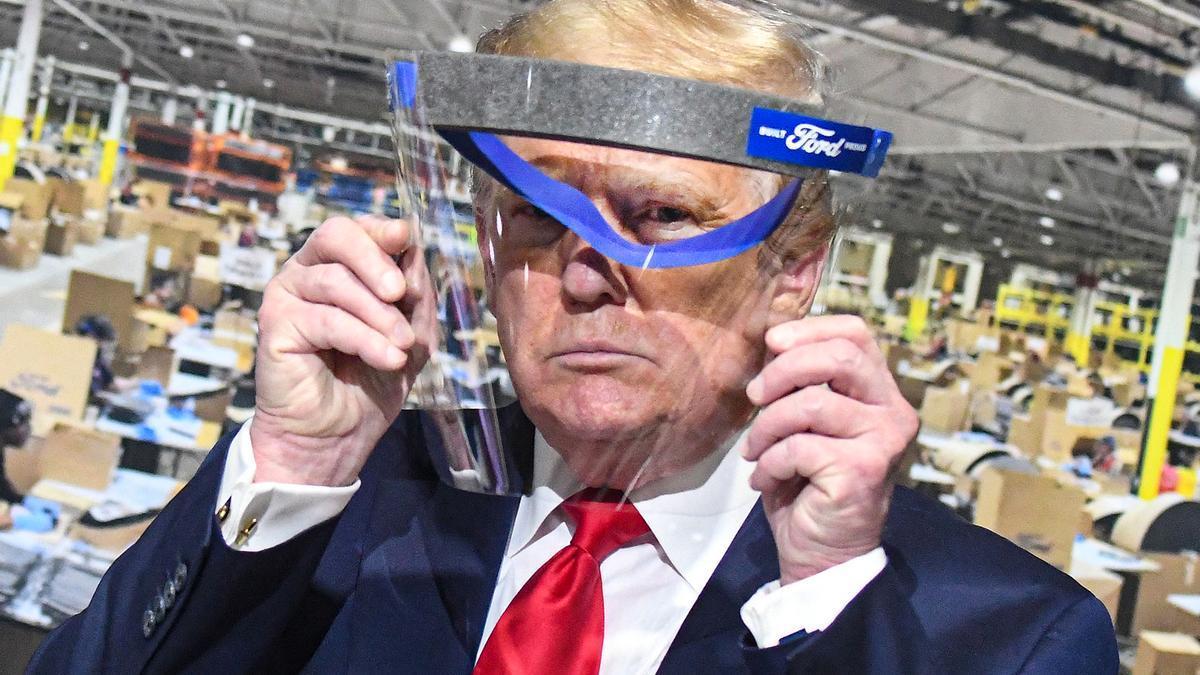 Trump posa con una pantalla protectora durante una visita a una planta de Ford en mayo de 2020.