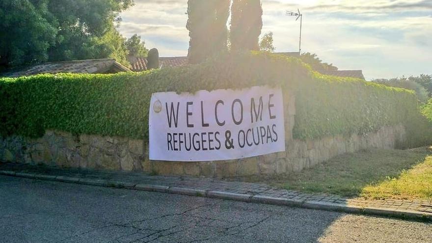 Jóvenes de Vox colocan una pancarta en el chalé de Iglesias y Montero con el lema 'Welcome Refugees & Ocupas'