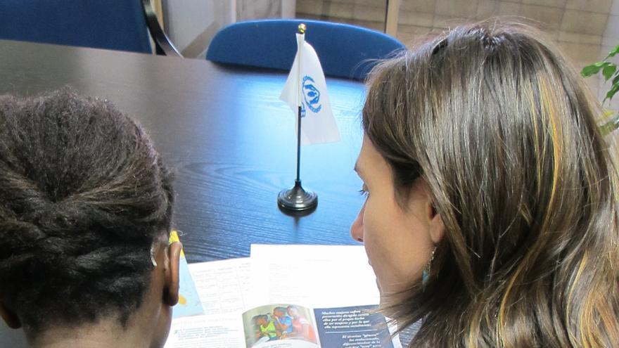 Personal de ACNUR explica a una mujer el sistema de asilo de España. / Fotografía: ACNUR