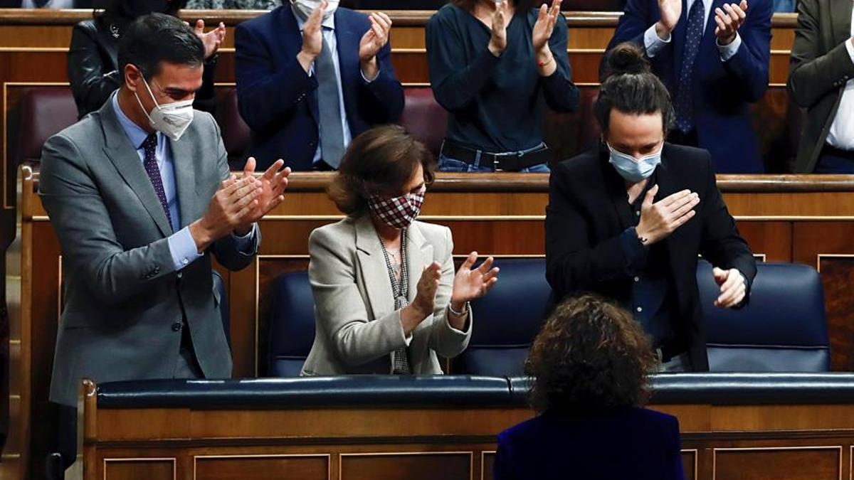 La ministra de Hacienda, María Jesús Montero, aplaudida por el presidente del Gobierno, Pedro Sánchez, y los vicepresidentes, Carmen Calvo y Pablo Iglesias, en el Congreso.