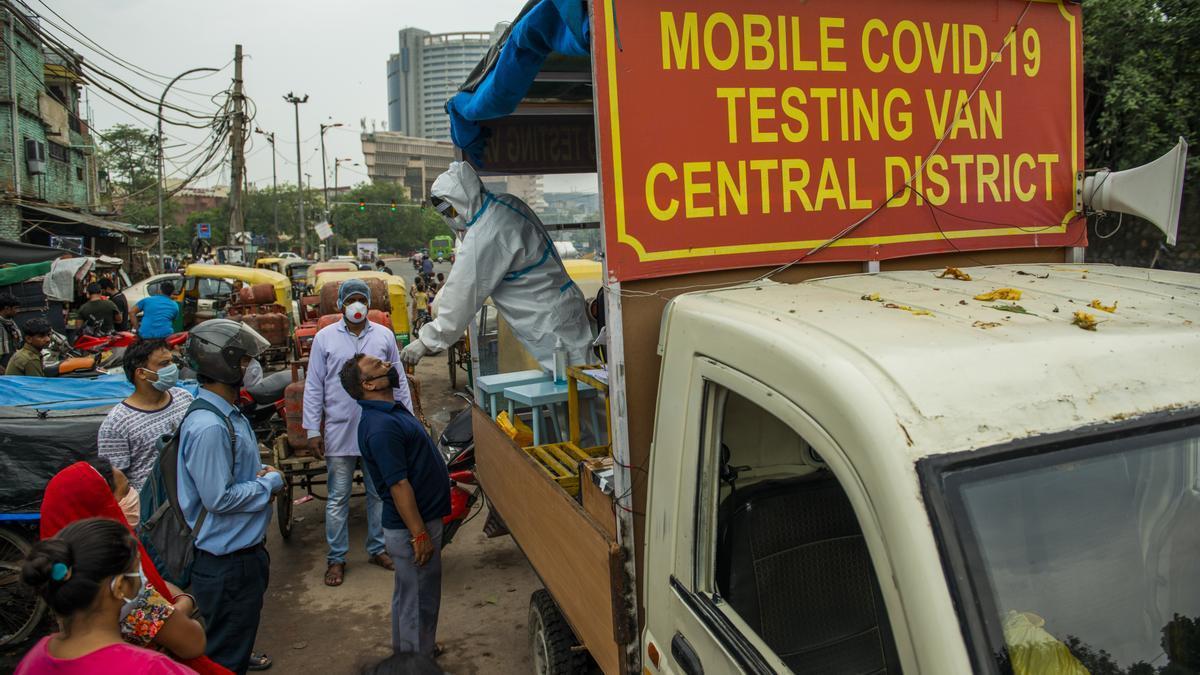 Un trabajador sanitario con traje protector en una camioneta móvil toma una muestra nasal de un hombre para hacerle la prueba de coronavirus.