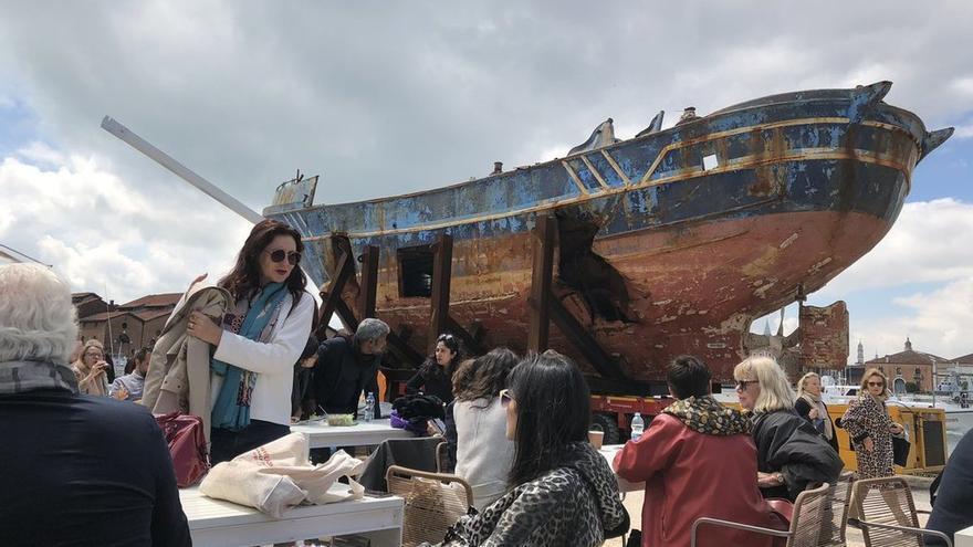 Un grupo de personas comiendo y bebiendo frente a la barcaza exhibida en una de las sedes de la Bienal de Venecia.