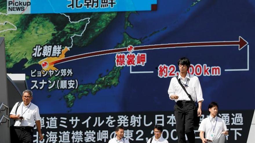 Los peatones caminan bajo un monitor a gran escala que muestra el vuelo de un misil balístico norcoreano sobrevolando Japón hoy, viernes 15 de septiembre de 2017, en Tokio (Japón).
