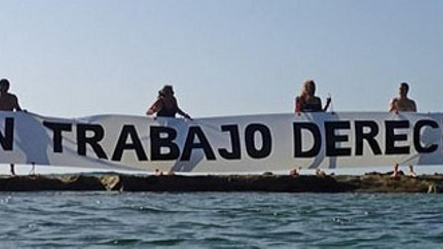 Una pancarta se despliega sobre la barra de Las Canteras para pedir 'Pan, trabajo y derechos'.