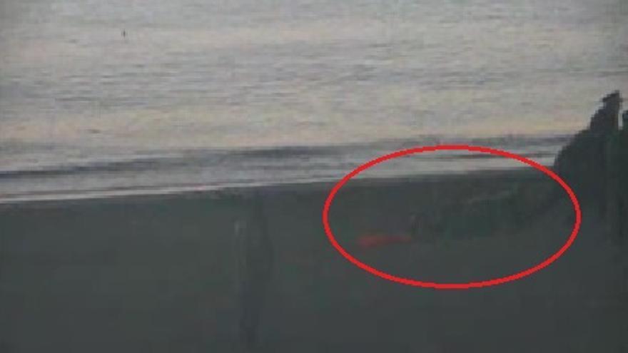 Un agente marroquí arrastra uno de los neumáticos o flotadores pinchados durante el intento de entrada a Ceuta. Fotograma de uno de los vídeos oficiales difundidos por el Ministerio de Interior.
