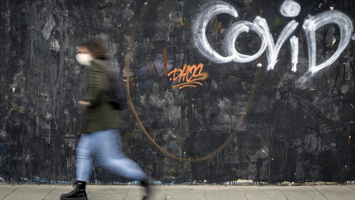 Una mujer pasa al lado de un grafitti del artista J.Warx