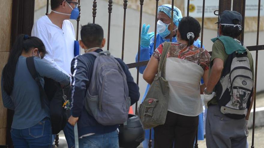 Familiares con tapabocas hacen consultas este miércoles a funcionarios para poder despedir a sus seres queridos, en un cementerio de Guayaquil (Ecuador).
