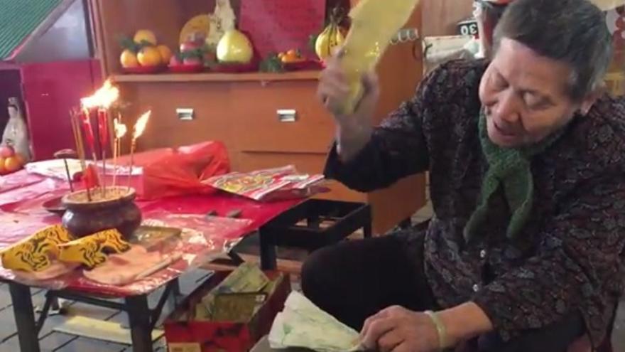 Captura de pantalla de un vídeo de the Guardian en el que aparece una hechicera de Hong Kong en medio de un ritual de magia negra