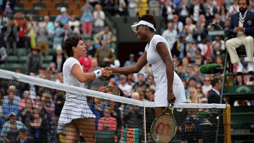 La tenista estadounidense Venus Williams (d) da la mano a la española Carla Suárez Navarro (i) tras su victoria en la cuarta ronda del torneo de Wimbledon