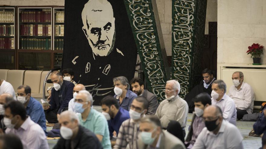 Decenas de personas con mascarilla durante una oración en un templo de Teherán (Irán)