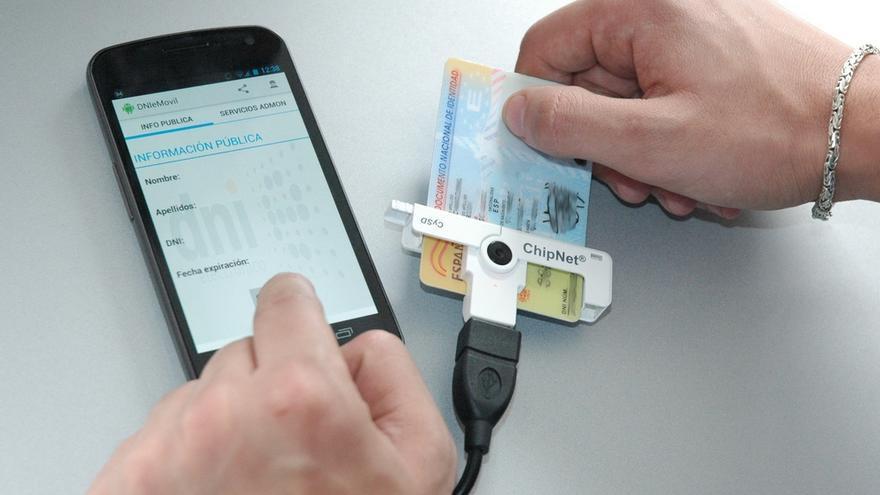 Un DNI electrónico junto a un lector de tarjetas Android