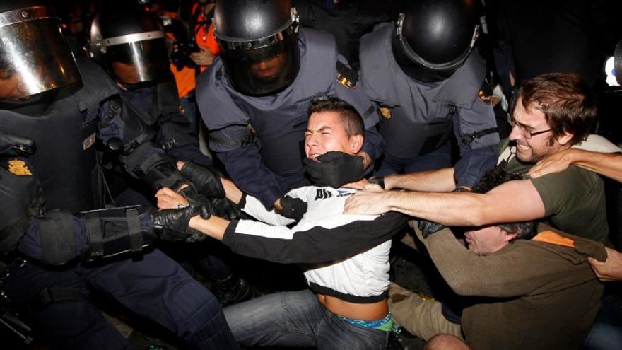 Los antidisturbios mueven a un manifestante que ejerce resistencia pasiva