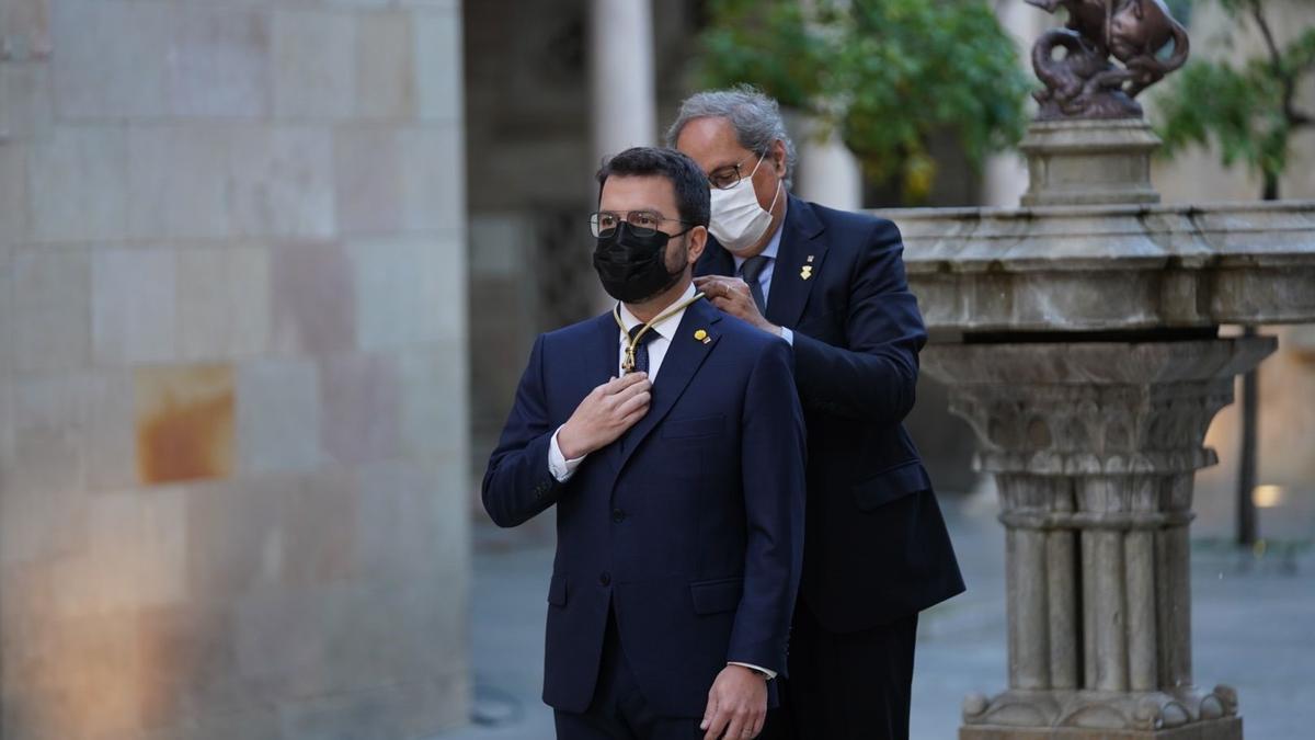El expresidente Quim Torra pone la medalla de presidente de la Generalitat a Pere Aragonès