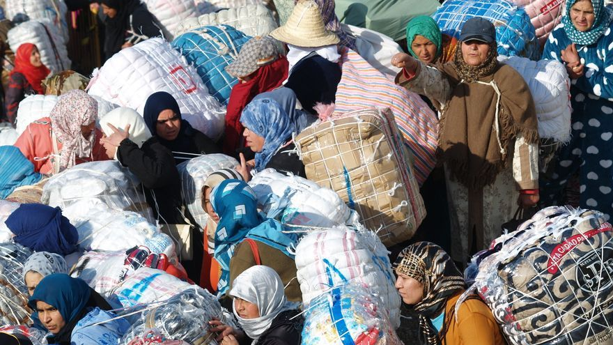 Decenas de porteadoras esperan entrar en Ceuta con los fardos sobre sus espaldas.