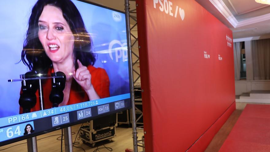 El escenario donde el PSOE ha evaluado los comicios a la Asamblea de Madrid, vacío. A la izquierda de la imagen, Isabel Díaz Ayuso celebra la victoria