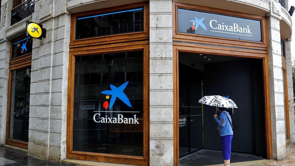 En la imagen, una mujer observa el interior de la sede de Caixabank en la plaza del Ayuntamiento de Valencia. EFE/Manuel Bruque/Archivo