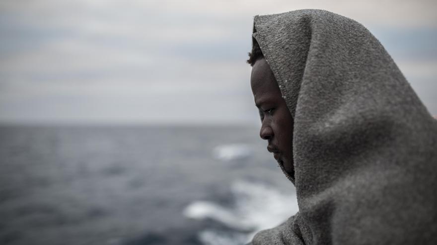 Una de las personas rescatadas se cubre del viento frío con una manta en la popa del barco Open Arms / Olmo Calvo